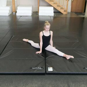 Woman practices in a gymnasium on the Gymnastics Tumbling Mats